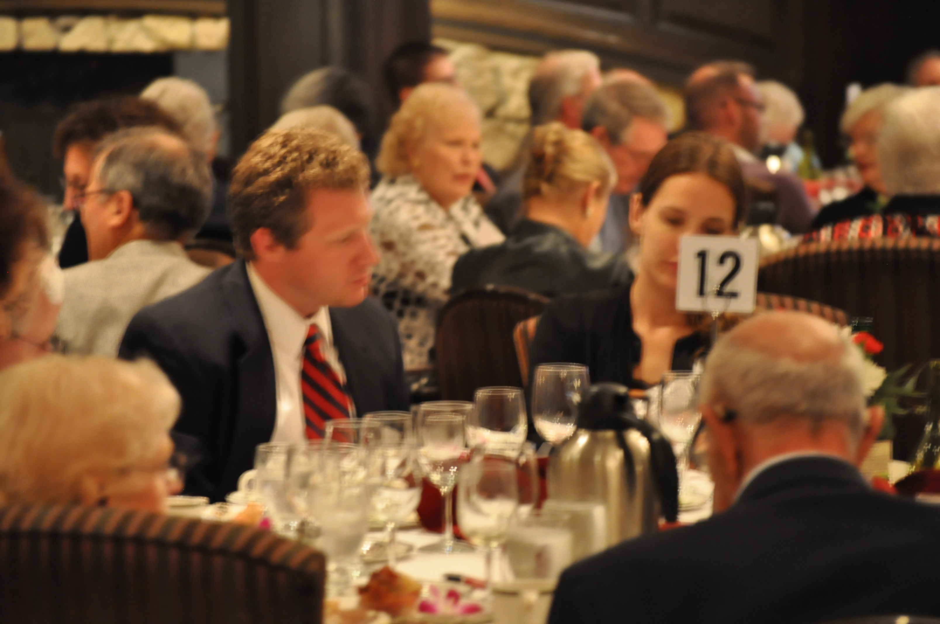 People at a table eating and listening during the Benefit Dinner